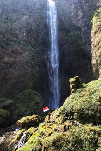 Man holding flag standing against waterfall