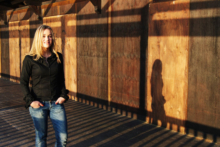 Portrait of blonde woman casting shadow against wooden wall at sunset