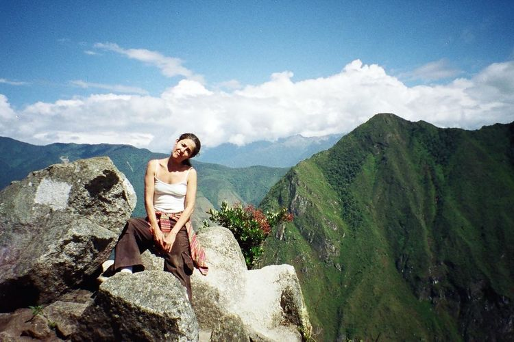Woman sitting on rock at machu picchu against sky