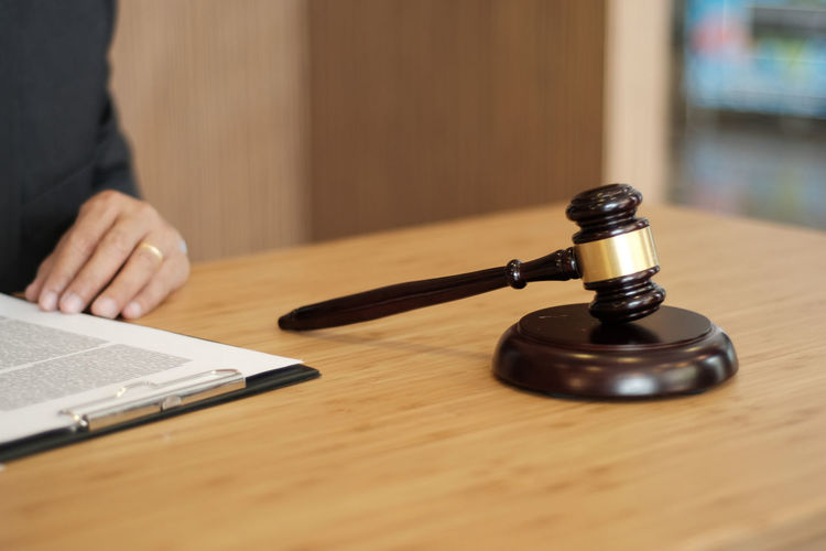Midsection of judge writing in paper on table