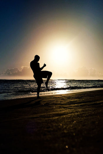 Silhouette Athlete Practicing Kickboxing At Beach Against Clear Sky During Sunset