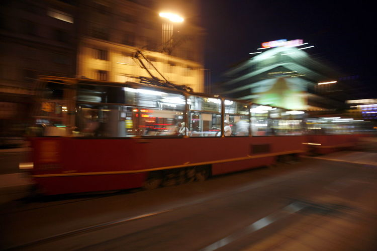 Arts Culture And Entertainment Blurred Motion Car City City Life City Street Depth Of Field Illuminated Incidental People Land Vehicle Mode Of Transport Night On The Move Public Transportation Selective Focus Speed Street The Way Forward Train Transportation Travel Urban