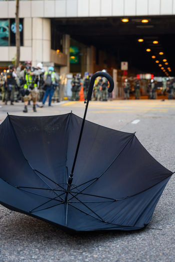 Close-up of wet umbrella on street in city