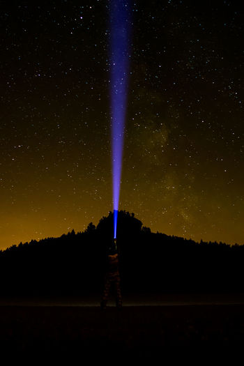 Silhouette man pointing flashlight towards star field in sky at night