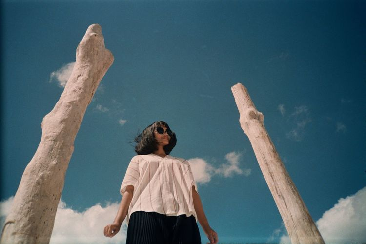 Rear view of woman standing by wooden poles against sky