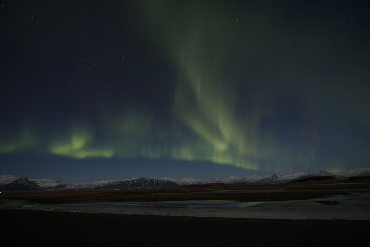 Low angle view of aurora borealis over mountains and lake