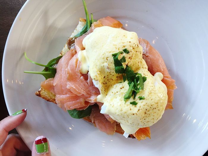 Close-up of cropped hands of woman holding eggs benedict served in plate