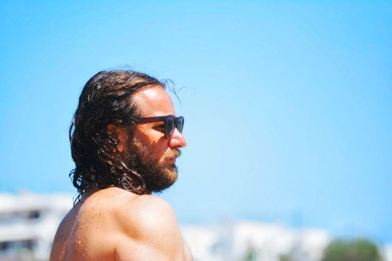 Side view of shirtless man wearing sunglasses against blue sky