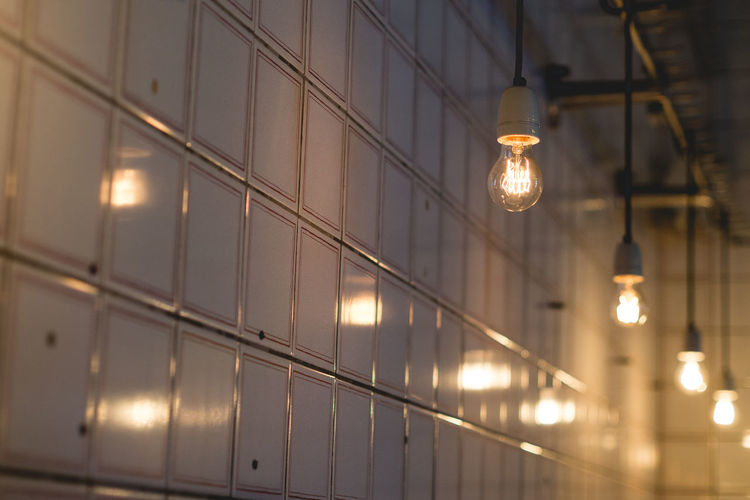 Low Angle View Of Light Bulbs Hanging Against Lockers