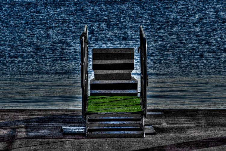Empty chairs on beach against sea