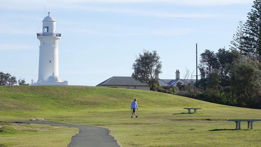 Man by lighthouse against sky