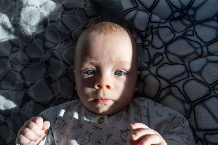 Little child with blue eyes lioks in camera