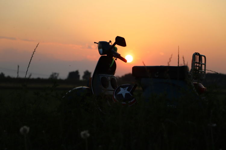Silhouette man on field against sky during sunset