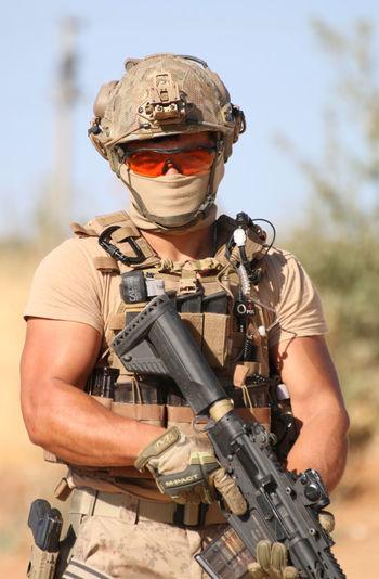 Portrait of soldier standing on field