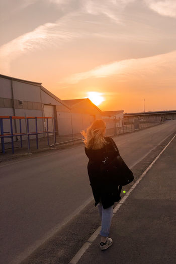 Rear view of woman standing on road against sky during sunset