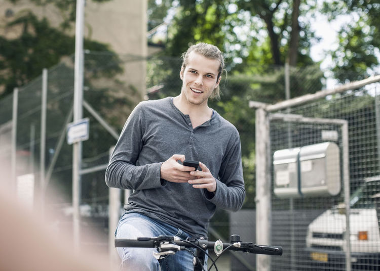 Side view of a young man using smart phone
