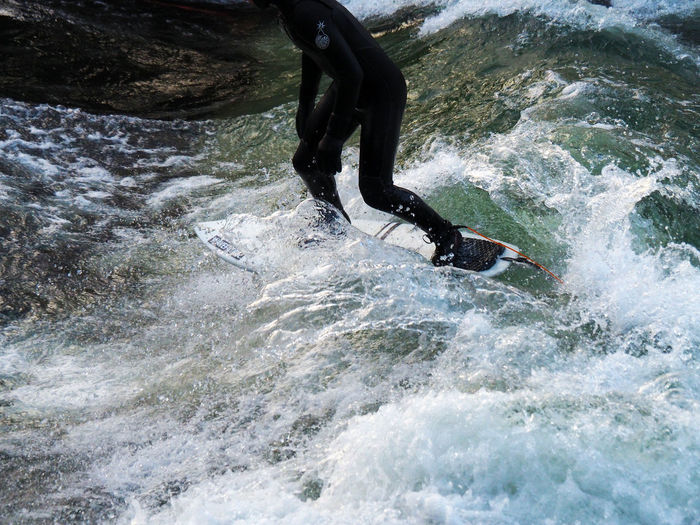 Adventure Cold Day Extreme Sports Leisure Activity Lifestyles Low Section Motion One Person Outdoors Real People Sea Speed Splashing Surf Surfer Surfing Unrecognizable Person Vitality Water Wetsuit Sport