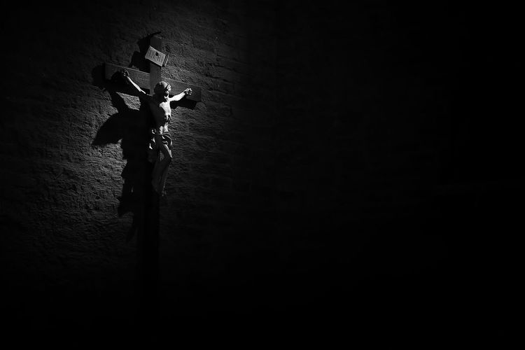 Low angle view of silhouette person against illuminated wall
