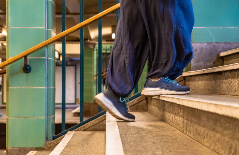 Low section of person walking on staircase