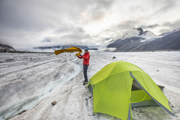Man with umbrella on snowcapped mountain against sky
