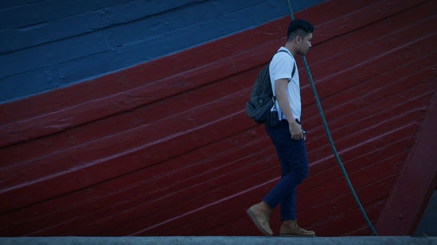 Side view of young man with backpack walking on retaining wall