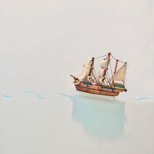 Close-up of toy ship floating on water against white background