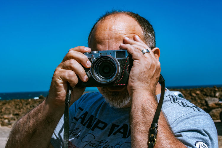 Close-up of mature man photographing with camera against blue sky
