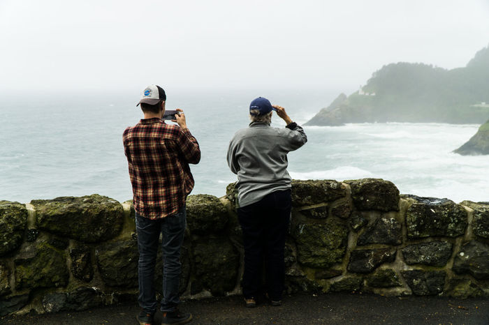Heceta Head Light House in the fog, two tourists Beauty In Nature Coastline Danger Day Friendship Full Length Leisure Activity Men Mountain Nature Oerlinghausen Oregon Coast Oregonexplored Outdoors Real People Rear View Rock - Object Sea Sky Standing Togetherness Tranquility Two People Warning Water
