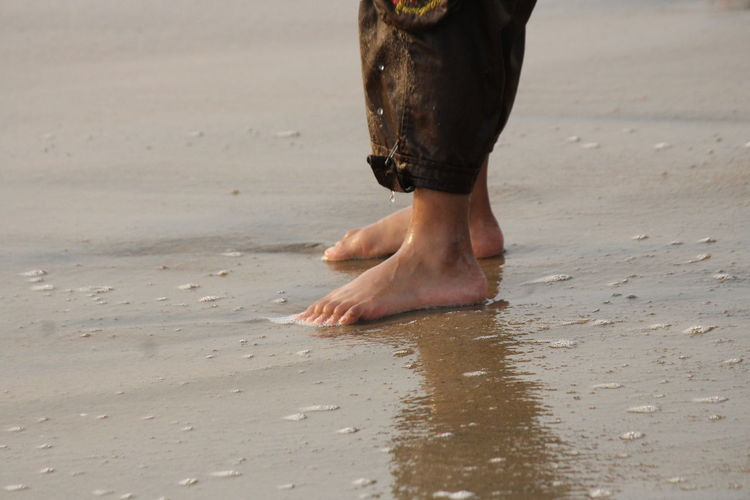 Low section of man walking on wet beach