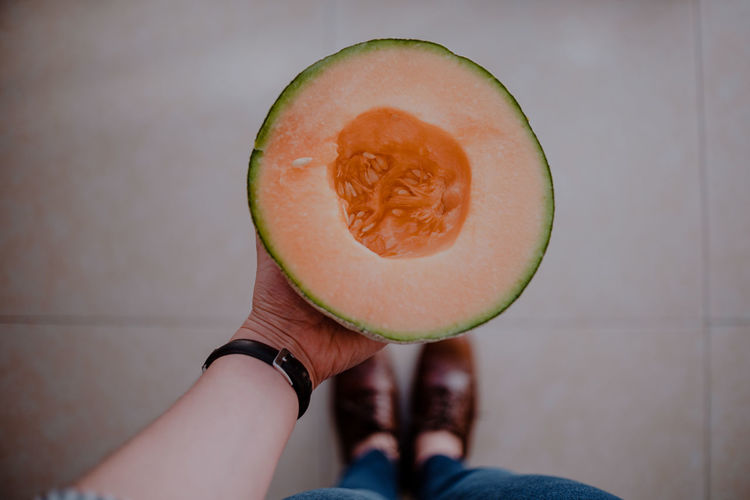 Midsection of person holding melon