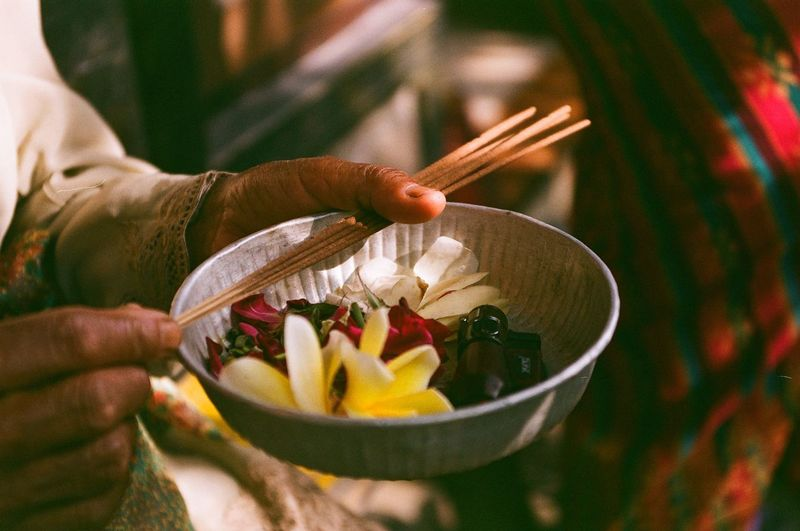 Close-up of hands holding flowers in bowl and incenses