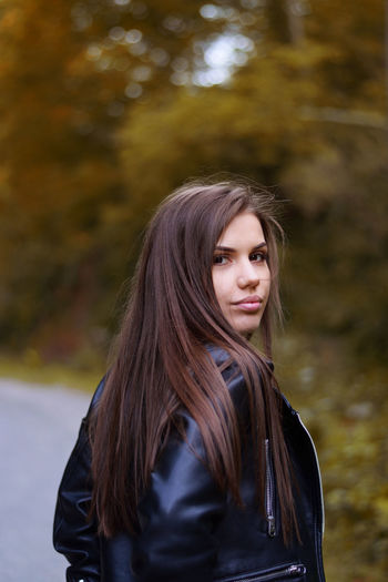 Portrait of beautiful young woman standing on footpath