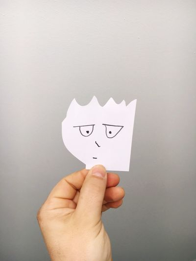 Close-up of hand holding paper with face drawn on it