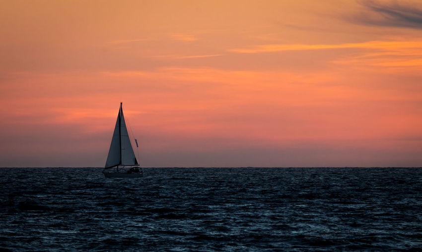 Sailboat sailing on sea against orange sky