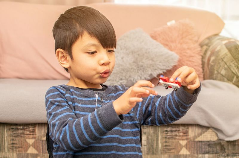 Boy playing with toy car at home