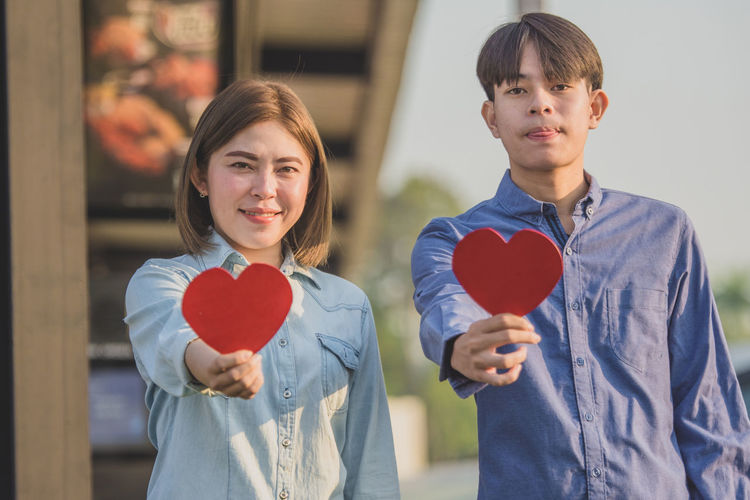 Portrait of smiling couple holding heart shape while standing outdoors