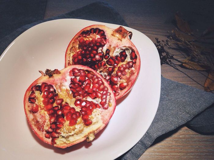 High angle view of halved pomegranate in plate on table
