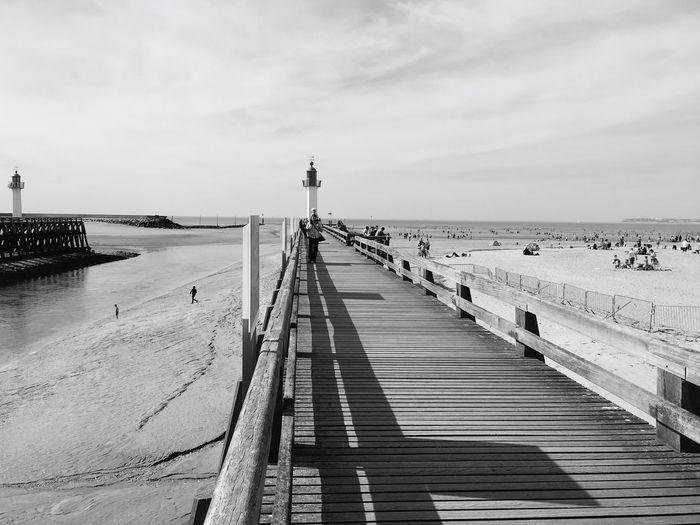 Pier Leading Towards Lighthouse At Beach Against Sky