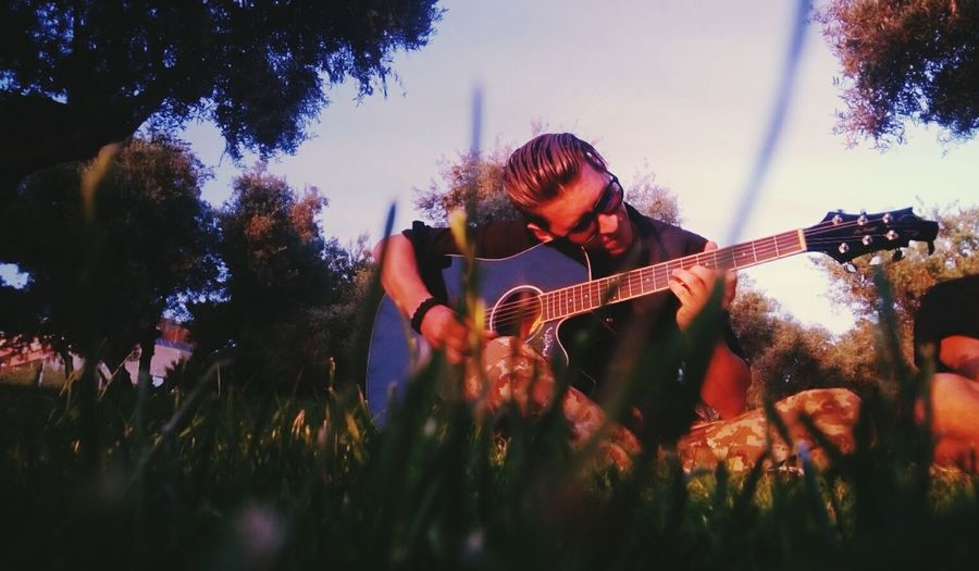 Man playing guitar against trees