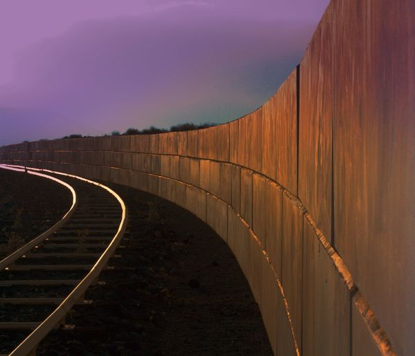 Railroad track by surrounding wall against sky during sky during sunset