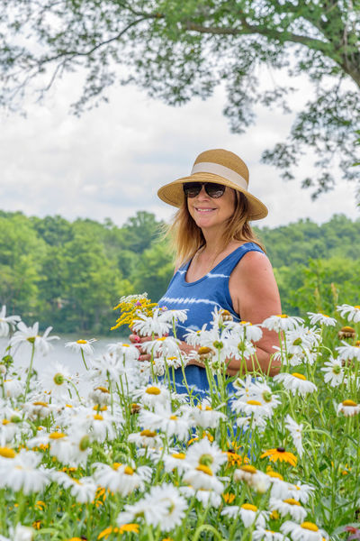 Woman Sunhat Outdoors Nature Water garden Picking Flowers  Lakeside Lake House  Happy People