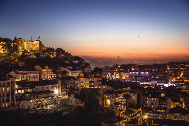 High angle view of illuminated cityscape of lisbon, against clear sky at sunset.