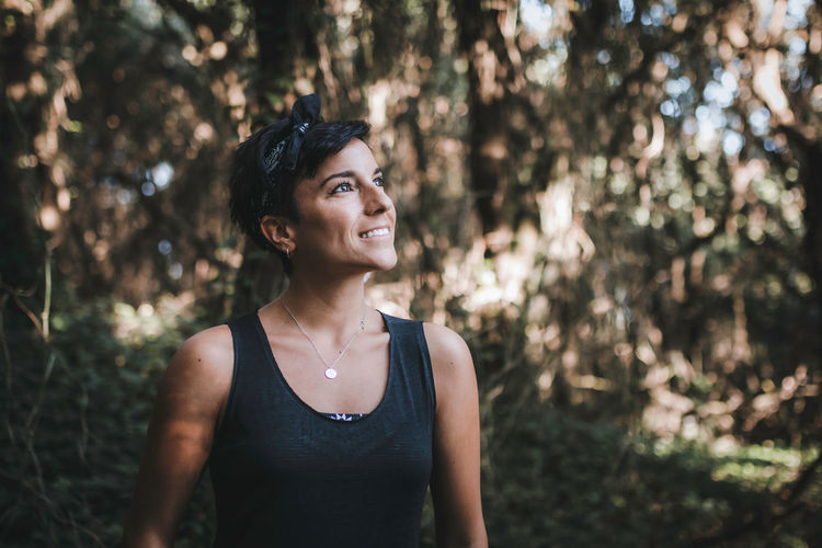 Smiling woman standing in forest