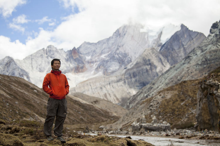 Portrait of smiling man standing on mountain against sky
