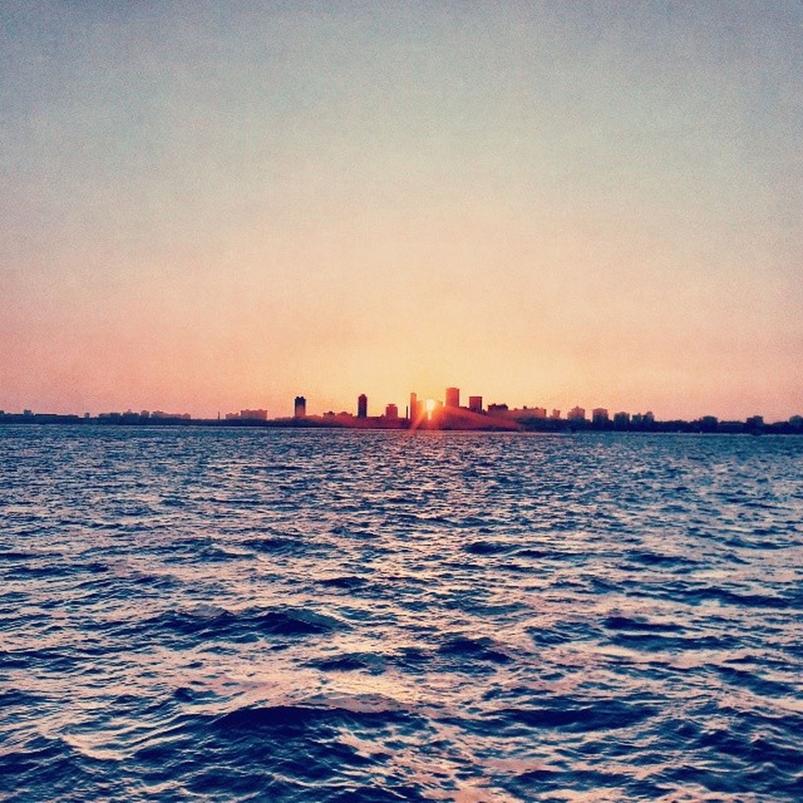 waterfront, water, sunset, sea, rippled, copy space, clear sky, building exterior, scenics, built structure, architecture, tranquil scene, tranquility, beauty in nature, nature, sky, city, silhouette, orange color, outdoors