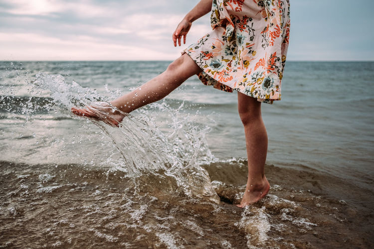 Midsection of woman splashing water at beach against sky