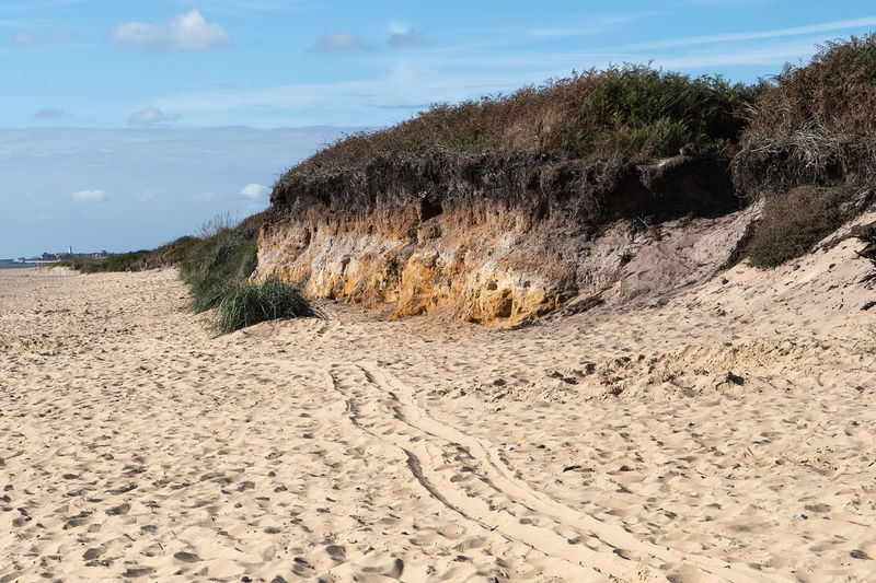 Sand dune on beach against sky