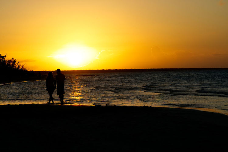 Couple walking on the beach at sunset Sunset Sky Sea Water Silhouette Two People Beach Land Beauty In Nature Togetherness Orange Color Scenics - Nature Horizon Nature Leisure Activity Horizon Over Water People Standing Real People Couple - Relationship Positive Emotion Outdoors