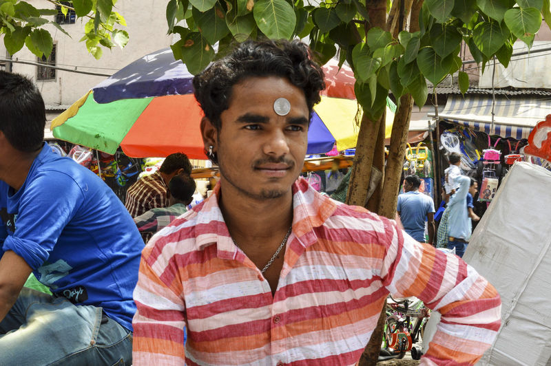 Portrait of young man standing in market
