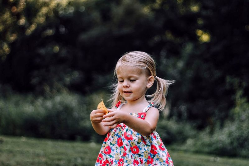 EyeEm Selects Childhood Real People Casual Clothing Focus On Foreground Girls One Person Front View Leisure Activity Outdoors Cute Elementary Age Day Holding Lifestyles Standing Fruit Food Nature Happiness Eating